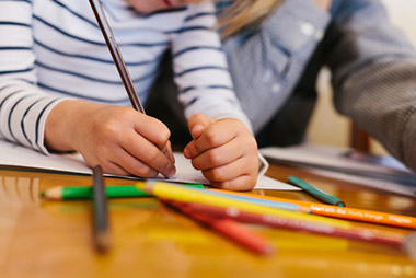 Ergotherapie-Blankenfelde-Kind-malt-mit-schriedenen-Stiften