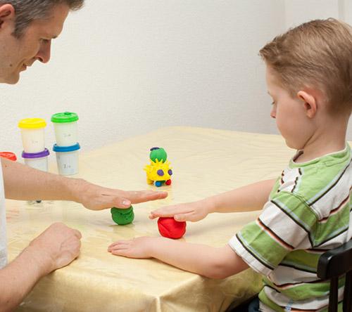 Ein Kind macht Übungen mit der Hand mit Hilfe von Knete